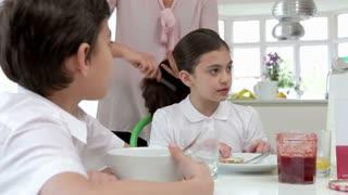 Schoolchildren Having Breakfast In Kitchen