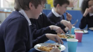 Schoolchildren Sitting At Table Eating Lunch