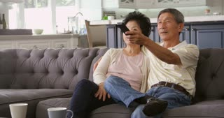 Senior Asian Couple At Home On Sofa Watching TV Shot On R3D