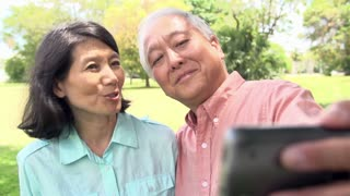 Senior Asian Couple Taking Selfie In Park Together