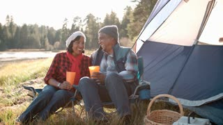 Senior black couple on a camping trip relax outside tent