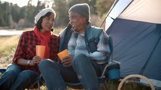 Senior black couple on camping trip outside tent, close up