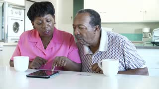 Senior Couple Booking Vacation Online Using Digital Tablet