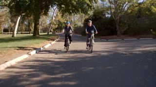 Senior Couple Cycling Through Park In Slow Motion