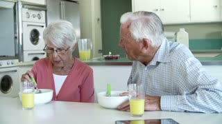 Senior Couple Having Breakfast In Kitchen Together