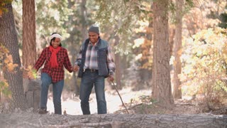 Senior couple in a forest walk to camera, on left of frame