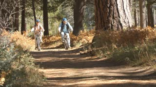 Senior couple riding bikes on a forest trail, handheld shot