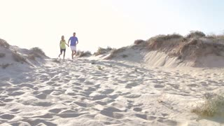 Senior Couple Running Down Sand Dune Together