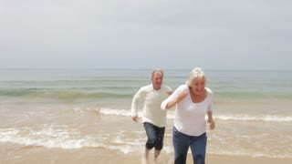 Senior Couple Running On Fall Beach