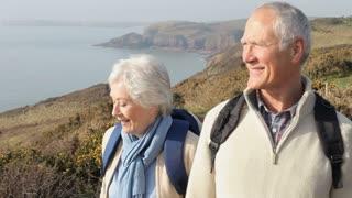 Senior Couple Taking Selfie Walking Along Coastal Path