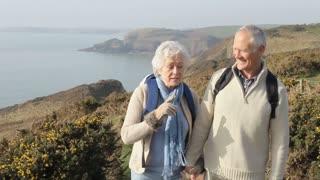 Senior Couple Walking Along Coastal Path And Taking Photo