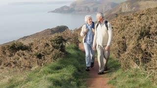Senior Couple Walking Along Coastal Path