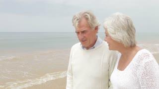 Senior Couple Walking Along Misty Beach