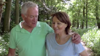 Senior Couple Walking Along Summer Path Together