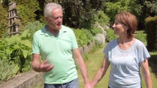 Senior Couple Walking Around Garden Together
