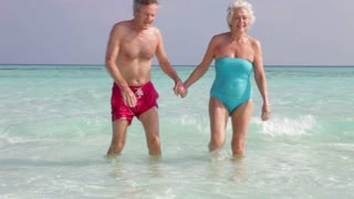 Senior Couple Walking Out Of Tropical Sea