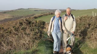 Senior Couple With Dog Walking Along Coastal Path