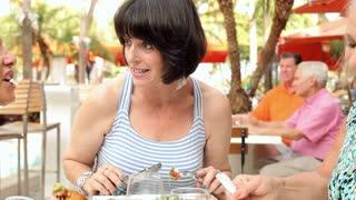 Senior Female Friends Eating Meal In Outdoor Restaurant