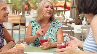Senior Female Friends Enjoying Cocktails In Bar Together
