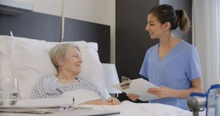 Senior Female Patient And Doctor Talking In Hospital Room