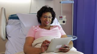 Senior Female Patient In Hospital Bed With Digital Tablet