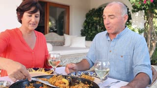 Senior Hispanic Couple Eating Paella At Home Together