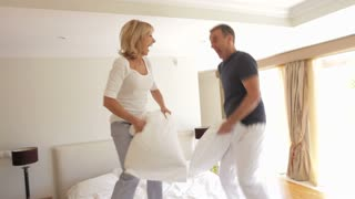 Senior husband and wife bouncing on bed having pillow fight together.Shot on Canon 5D Mk2 at at a frame rate of 30 fps