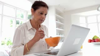 Senior Indian Woman Using Laptop Whilst Eating Breakfast