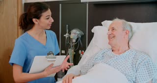 Senior Male Patient And Doctor Talking In Hospital Room
