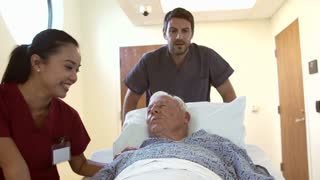 Senior Male Patient Being Wheeled Along Hospital Corridor