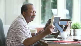 Senior Man Looking At Picture In Frame And Photo Album