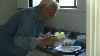 Senior Man With Poor Diet Making Sandwich In Kitchen
