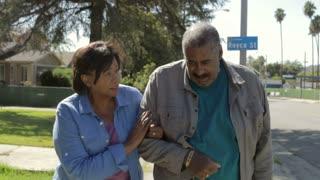 Senior Woman Helping Husband As They Walk Along Sidewalk