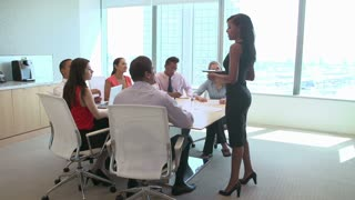 Seven Businesspeople Having Meeting Around Boardroom Table