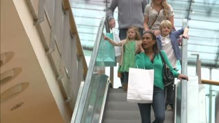 Shopper On Escalator In Shopping Mall Using Mobile Phone