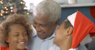 Slow motion sequence of boy and girl sitting on sofa with grandfather at Christmas time