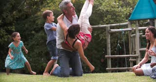 Slow Motion Sequence Of Families Playing In Garden Together