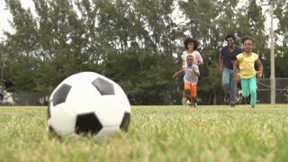 Slow Motion Sequence Of Family Playing Soccer In Park