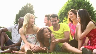 Slow Motion Sequence Of Friends Sitting On Grass Together