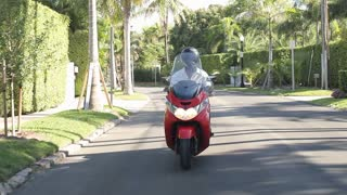 Slow Motion Sequence Of Man Riding Motor Scooter On Road