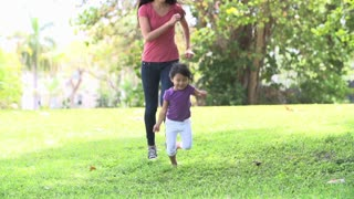 Slow Motion Sequence Of Mother And Daughter Running In Park