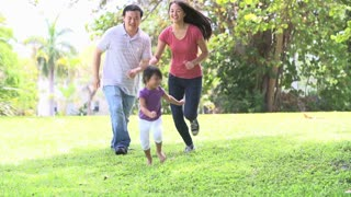 Slow Motion Sequence Of Parents And Daughter Running In Park