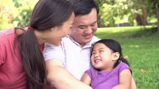 Slow Motion Sequence Of Parents Cuddling Daughter In Park