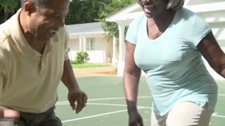 Slow Motion Sequence Of Senior Couple Playing Basketball
