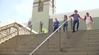 Slow Motion Sequence Of Teenagers Running Down Stairs