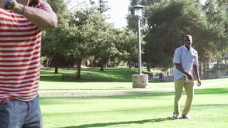 Slow Motion Sequence Of Two Men Playing Baseball In Park
