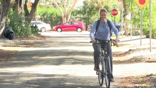 Slow Motion Sequence Of Woman Cycling Along Street To Work