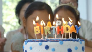 Slow Motion Shot As Girl Blows Out Candles On Birthday Cake