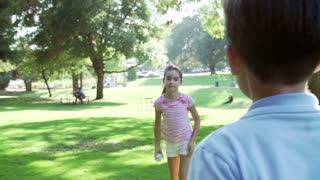 Slow Motion Shot Of Children Playing Catch With Ball In Park