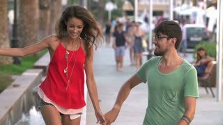 Slow Motion Shot Of Couple Dancing Along Street Together